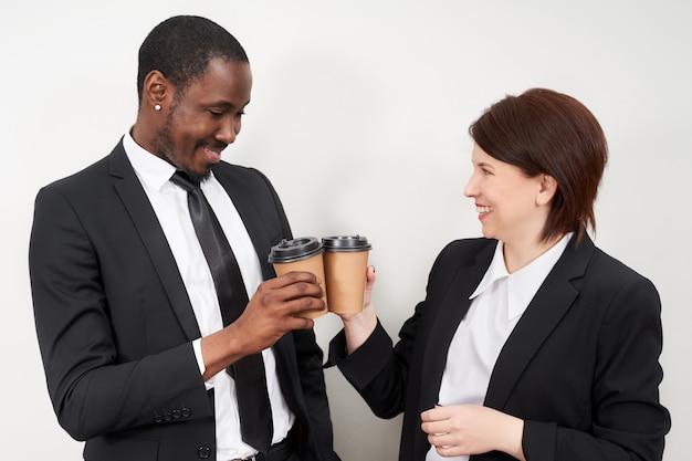 Neue unternehmenspartner, die nach abschluss des geschäfts einen kaffee rösten, kaukasische frau und afrikanischer mann