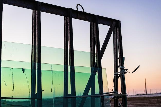 Neue versiegelte glaseinheiten auf der baustelle vor dem hintergrund eines sonnenuntergangshimmels. lagerung und vorbereitung beim einbau von fenstern. reflexion der abendsonne in neuen doppelglasfenstern.