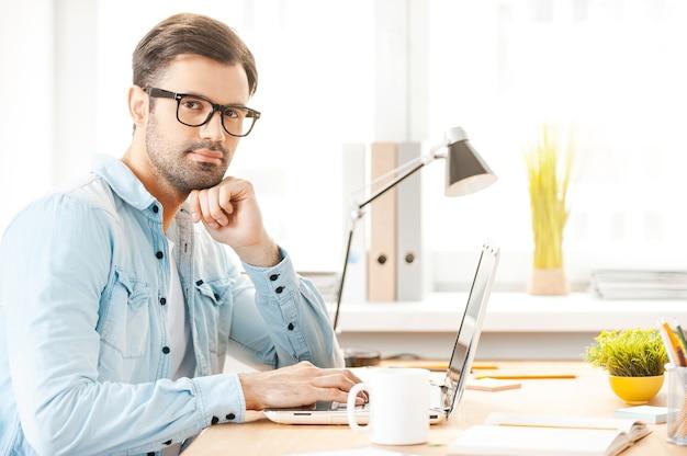 Neue visionen schaffen. hübscher junger mann in hemd und brille, der am laptop arbeitet und an seinem arbeitsplatz in die kamera schaut