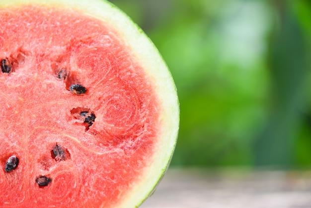 Neue wassermelonenscheibe halb auf naturgrün schließen sie herauf tropische frucht der wassermelone auf tabelle