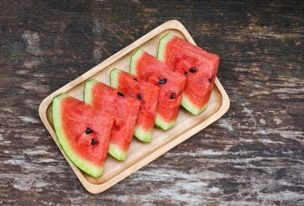 Neue wassermelonenscheibe - tropische frucht der wassermelone auf hölzernem behälter, draufsicht