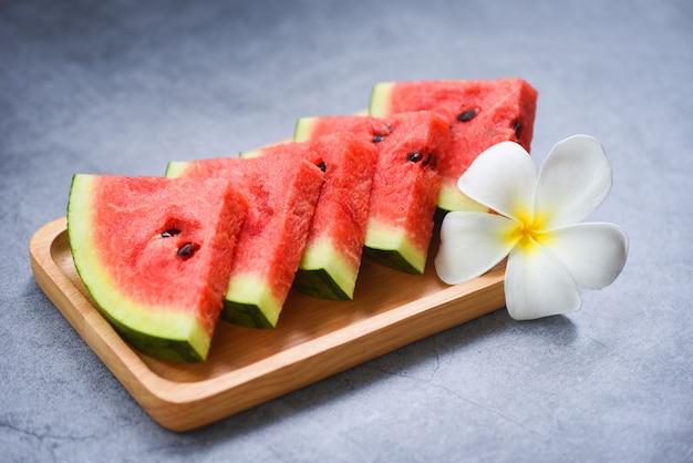 Neue wassermelonenscheibe und weiße blume auf hölzernem behälter