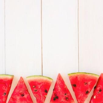 Neue wassermelonenscheiben in dreieckiger form auf hölzerner planke