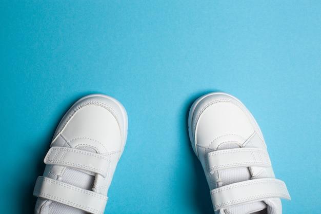 Neue weiße sportschuhe oder turnschuhe des kindes auf dem hellblauen pastellhintergrund auf der anderen seite davon. kopierplatz für text