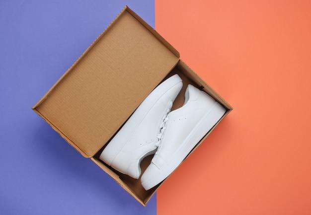 Neue weiße turnschuhe und box auf zwei tonnen papier