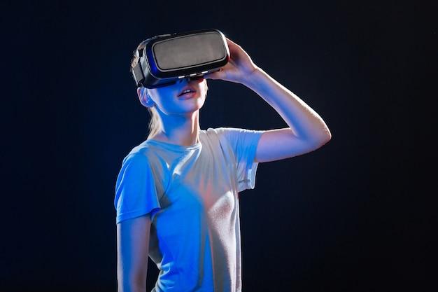 Neue welt. angenehme blonde frau, die 3d-brille hält, während virtuelle realität erfahren