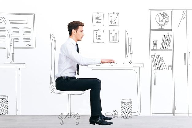 Neuer arbeitstag. seitenansicht eines gutaussehenden jungen mannes, der mit einem gezeichneten computer arbeitet, während er an seinem illustrierten arbeitsplatz sitzt