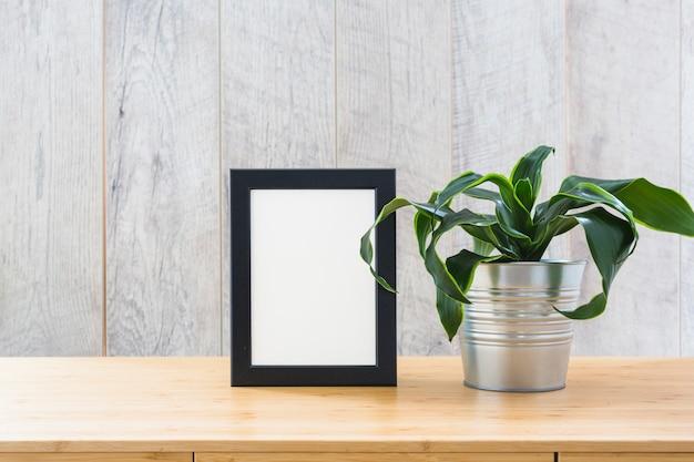 Neuer eingemachter zimmerpflanze- und fotorahmen auf dem hölzernen schreibtisch