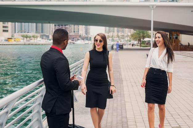 Neuer job in einer großstadt. zwei schöne geschäftsfrauen treffen sich mit ihrem neuen college bei dubai marine.