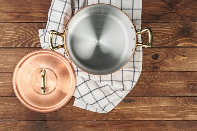 Neuer kupferner kochender topf auf holztisch, ansicht von oben