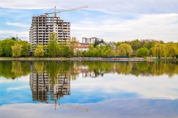 Neuer moderner wolkenkratzer im bau am ufer eines sees. betongebäudereflexion im wasser