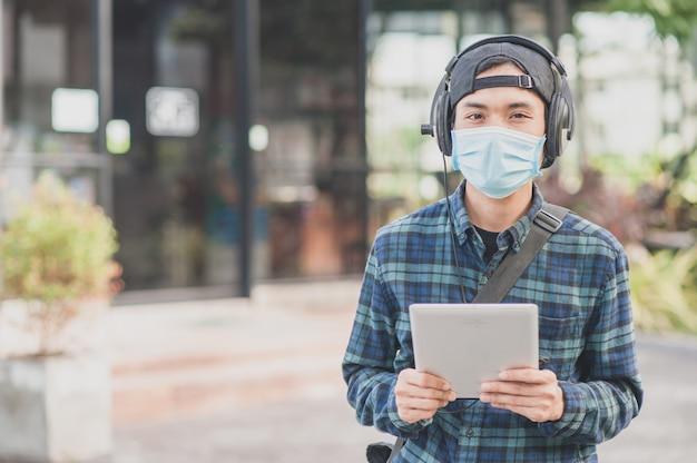 Neuer normaler asiatischer mann verwenden gesichtsmaske, die musik durch mobiles tablet-internet hört