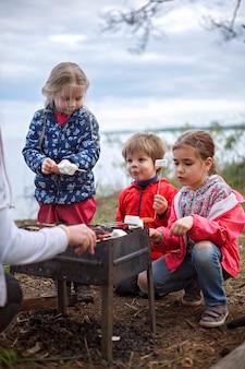 Neuer normaler fluchtschritt, wildes wandern in der natur und erholung mit der familie im freien. kinder am feuer stehen und marshmallows kochen, am wochenende wandern, lebensstil
