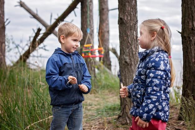 Neuer normaler fluchtschritt, wildes wandern in der natur und erholung mit der familie im freien. kinder haben spaß, während eltern käse und würstchen am feuer kochen, am wochenende wandern, lebensstil