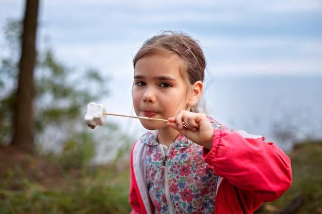 Neuer normaler fluchtschritt, wildes wandern in der natur und erholung mit der familie im freien. kinder kochen und probieren marshmallows, die am feuer gebraten werden, wandern am wochenende, lebensstil