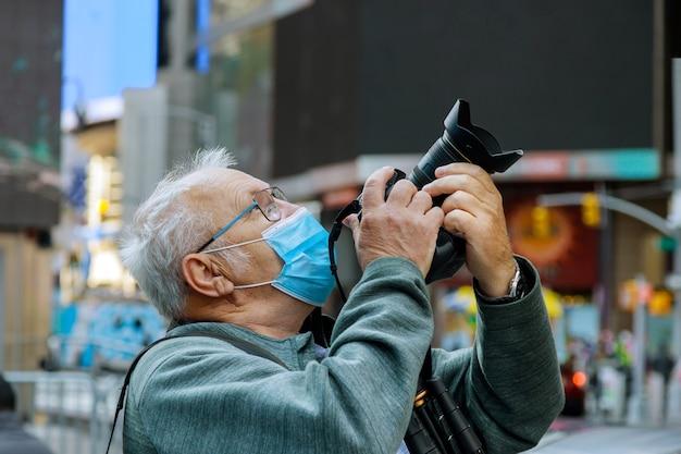 Neuer normaler tourismusmann in einer maske macht fotos von new york travel city tour während der sommerferien nach lockdown usa