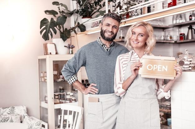 Neuer ort. erfreutes glückliches paar, das zusammen vor der theke steht und sein eigenes café eröffnet