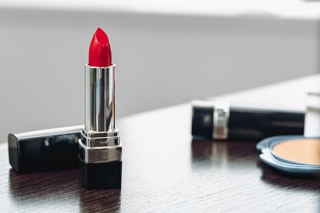 Neuer roter lippenstift auf schminktisch schließen oben