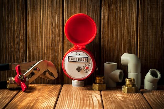 Neuer wasserzähler mit armaturen und schraubenschlüssel auf einem vintage-holzhintergrund. sanitäre ausstattung.