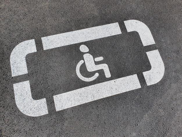 Neues behindertenschild auf dem neuen asphalt gemalt.