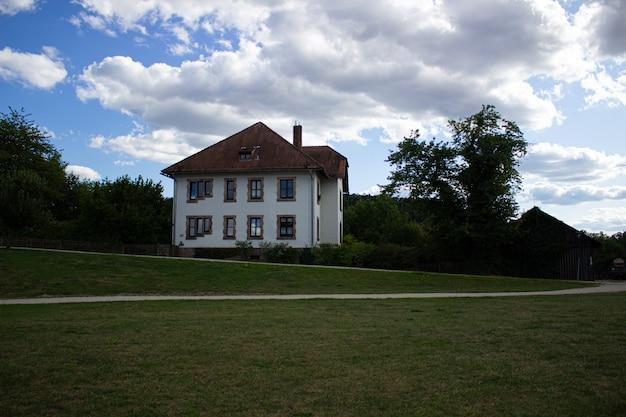 Neues einfamilienhaus auf der grünen wiese mit blauem himmel.