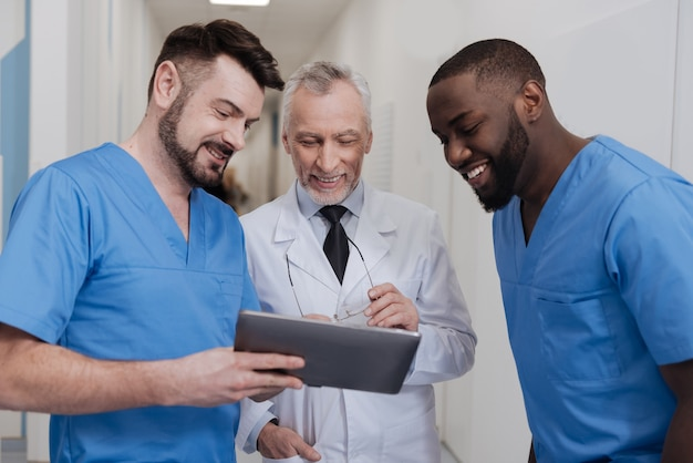 Neues gadget genießen. freudiger alter bärtiger praktizierender, der im krankenhaus steht und diskussion mit kollegen genießt, während kollegen modernes gerät halten
