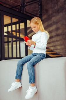 Neues gerät. konzentriertes blondes mädchen sitzt auf dem sofa und chattet online mit ihrer freundin