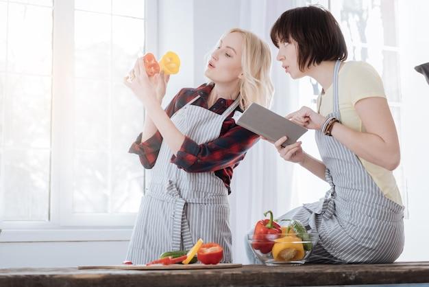 Neues gericht. angenehme nette junge frau, die ein notizbuch hält und ein rezept liest, während sie mit ihrer freundin in der küche ist