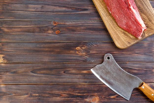 Neues großes stück schweinefleisch auf einem hölzernen schneidebrett mit küchenaxt. draufsicht über grauen konkreten hintergrund