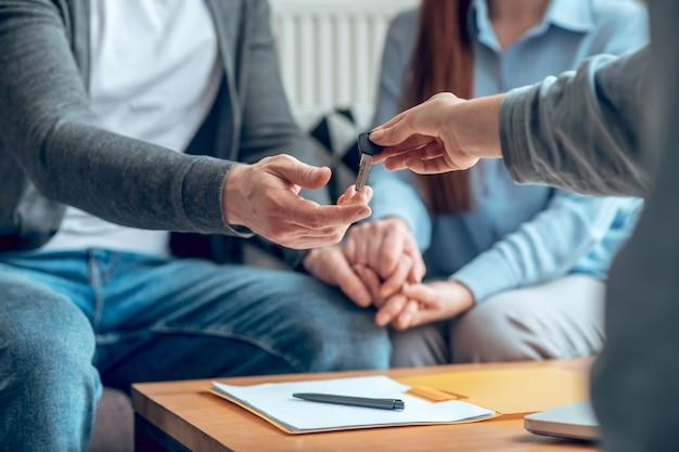 Neues haus. makler geben dem käufer optimistisch den schlüssel zum neuen haus im büro über dem tisch mit unterschriebenem dokument, kein gesicht