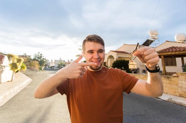 Neues haus wohnungseigentümer und menschen konzept nahaufnahme von schlüsseln, die jungen glücklichen mann mit neuen zeigen showing