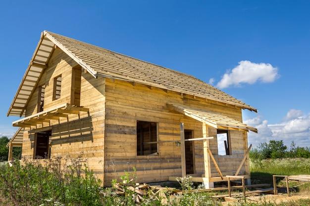 Neues hölzernes ökologisches traditionelles häuschen von natürlichen bauholzmaterialien mit dem steilen dach im bau in der grünen nachbarschaft