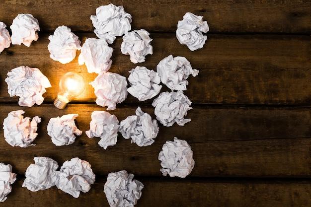 Neues ideenkonzept mit zerknittertem büropapier und glühbirne