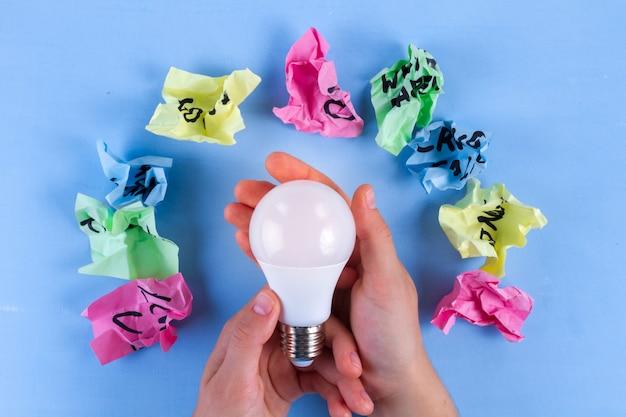 Neues ideenkonzept, zerknitterte papierbälle und glühlampe in den händen