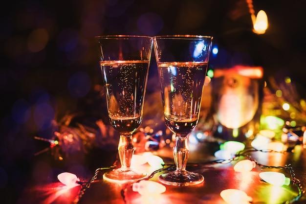 Neues jahr 2018. die gläser champagner. wunderkerzen. weihnachten. hintergrund bokeh lights girlande