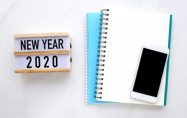 Neues jahr 2020 auf hölzernem kasten, leerem notizbuchpapier und telefon mit leerem bildschirm auf weißem marmortabellenhintergrund