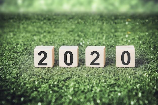 Neues jahr 2020 auf hölzernen würfeln mit grünem hintergrund.