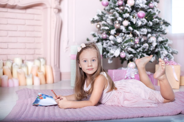 Neues jahr 2020! das konzept von weihnachten, ferien und kindheit. nettes baby schreibt santa claus einen brief nahe dem weihnachtsbaum im kinderzimmer. kleines mädchen, das zu hause auf weihnachten wartet