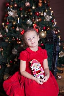 Neues jahr 2020! frohe weihnachten, schöne feiertage! ein entzückendes kleines mädchen mit einem nussknacker in ihren händen sitzt auf einem stuhl in einem schön verzierten innenraum des neuen jahres mit einem weihnachtsbaum. winter