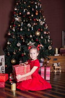 Neues jahr 2020! frohe weihnachten, schöne feiertage! kleines mädchen hält ein geschenk, lächelt, freut sich und erwartet weihnachten, neujahr und urlaub. ein gemütliches haus, ein brennender kamin und ein weihnachtsbaum. winter