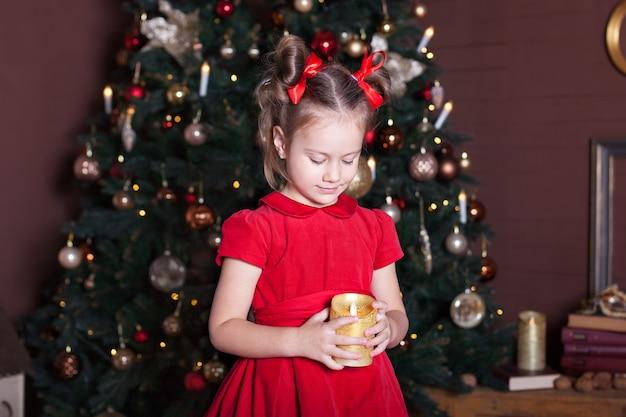 Neues jahr 2020. frohe weihnachten, schöne feiertage. nahaufnahmeporträt eines kleinen mädchens mit einer kerze. kleines mädchen hält eine kerze in ihren händen vor einem weihnachtsbaum. silvester. heiligabend.