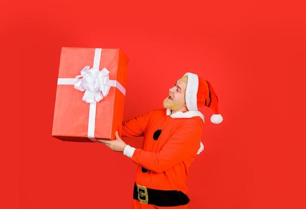 Neues jahr präsentiert weihnachtsmann mit großer geschenkbox lächelnder mann im weihnachtsmann-kostüm mit weihnachtsgeschenk