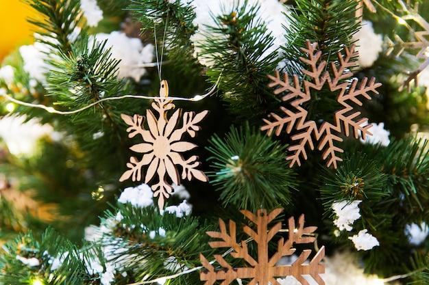 Neues jahr spielt in form von hölzernen schneeflocken auf weihnachtsbaum. dekorationen für das neue jahr