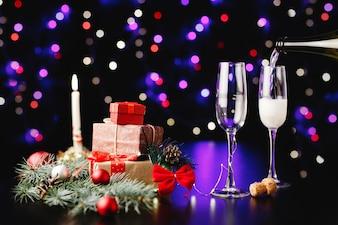 Neues Jahr und Weihnachtsdekor. Jemand gießt Champagner in die Gläser
