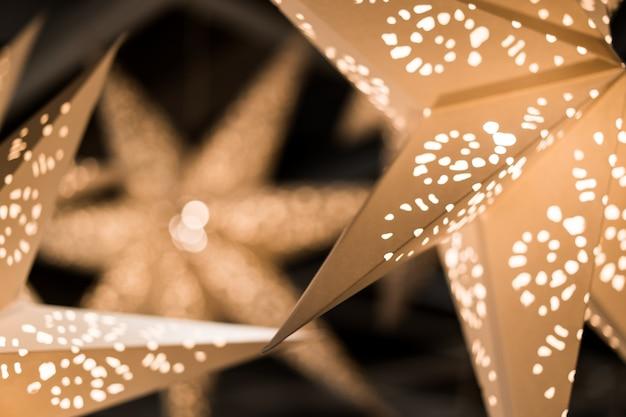 Neues jahr und weihnachtskonzept, dekorative papiersterne, voller löcher, warme lichter in der dunklen nacht