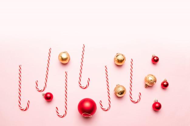 Neues jahr-weihnachten mit zuckerstangen, gold und roten bällen auf rosa hintergrund. flache lage, draufsicht, copyspace