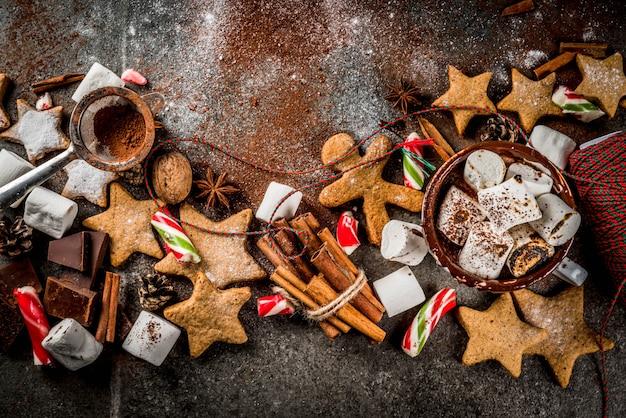 Neues jahr, weihnachtsleckerbissen, süßigkeiten. tasse heiße schokolade mit gebratenem eibisch, ingwersternplätzchen, lebkuchenmännern, gestreifter süßigkeit, gewürzzimtanis, kakao, puderzucker. draufsicht copyspace