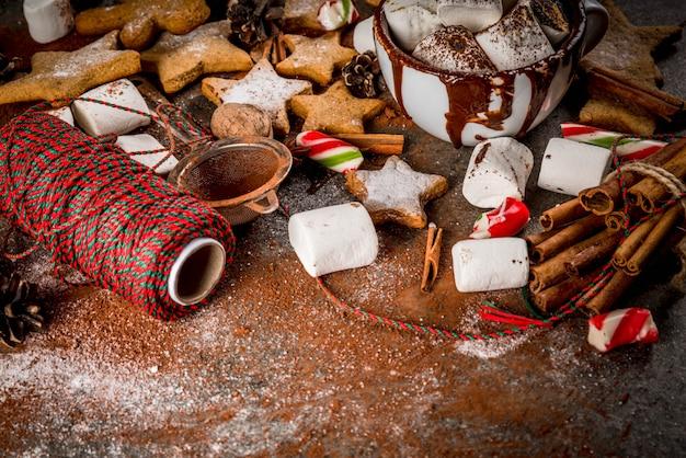 Neues jahr, weihnachtsleckerbissen, süßigkeiten. tasse heiße schokolade mit gebratenem eibisch, ingwersternplätzchen, lebkuchenmännern, gestreifter süßigkeit, gewürzzimtanis, kakao, puderzucker.