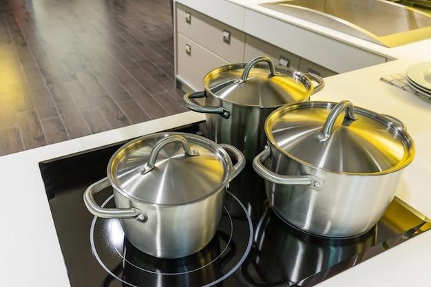 Neues kochgeschirr stellte auf den induktionsherd in der modernen küche ein