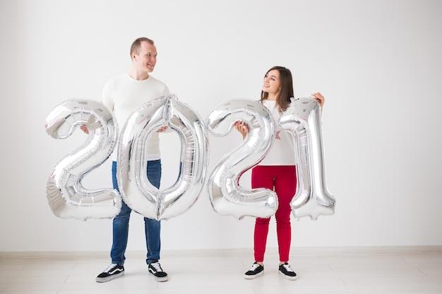 Neues konzept für das jahr 2021 - glücklicher junger mann und frau halten silberfarbene zahlen